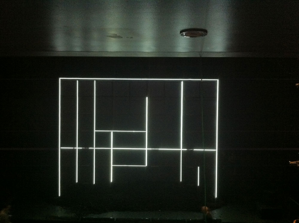 The backdrop of The Wasp is a black wall with neon lights in an abstract shape