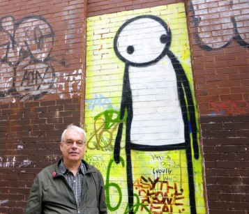 Claude posing by a mural by Stik