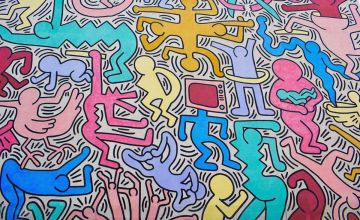 Colourful mural by Keith Haring with dancing human-like figures