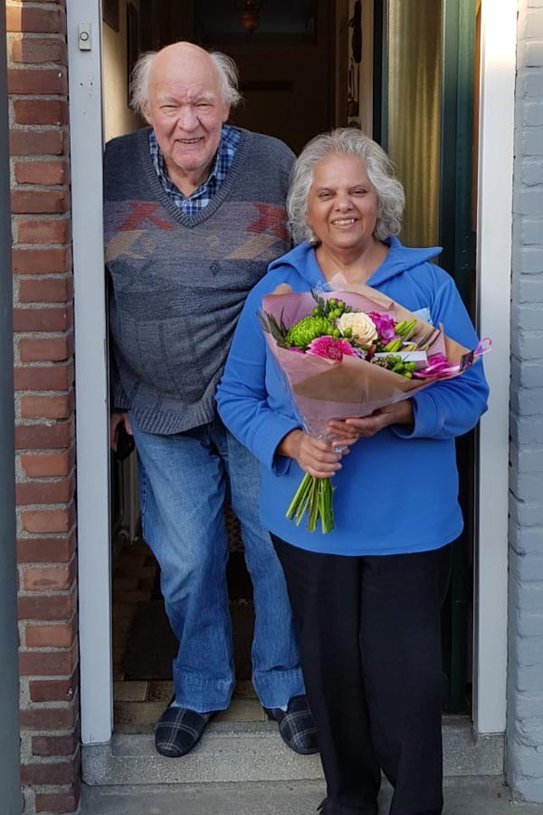 my parents at the door with a surprise bouquet delivery for their anniversary