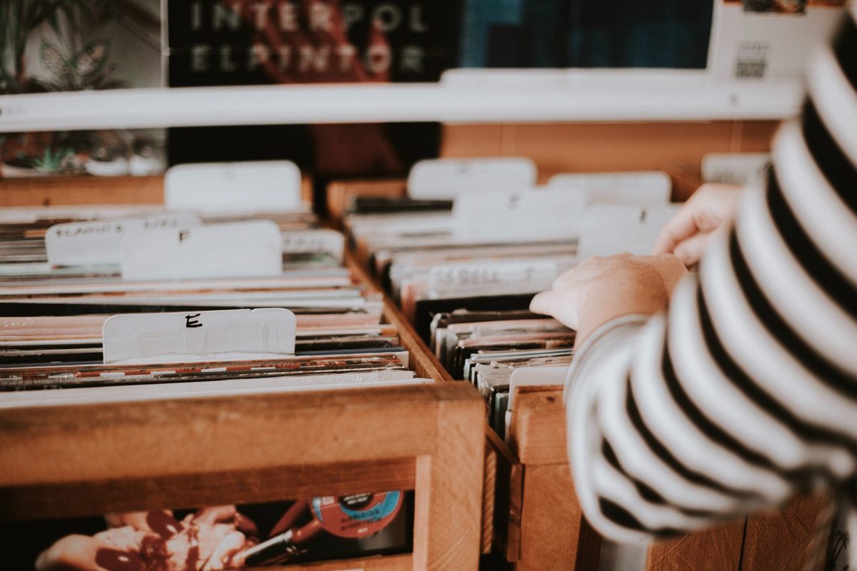 close-up of someone's hands browsing through crates of vinyl records