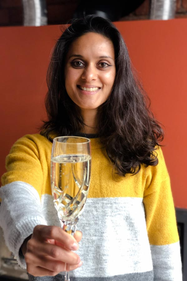 Photo of me holding a glass cava out towards the viewer