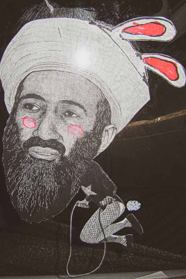 Shoreditch paste-up by HIN of Osama bin Laden with bunny ears wearing fishnet tights while rope-skipping