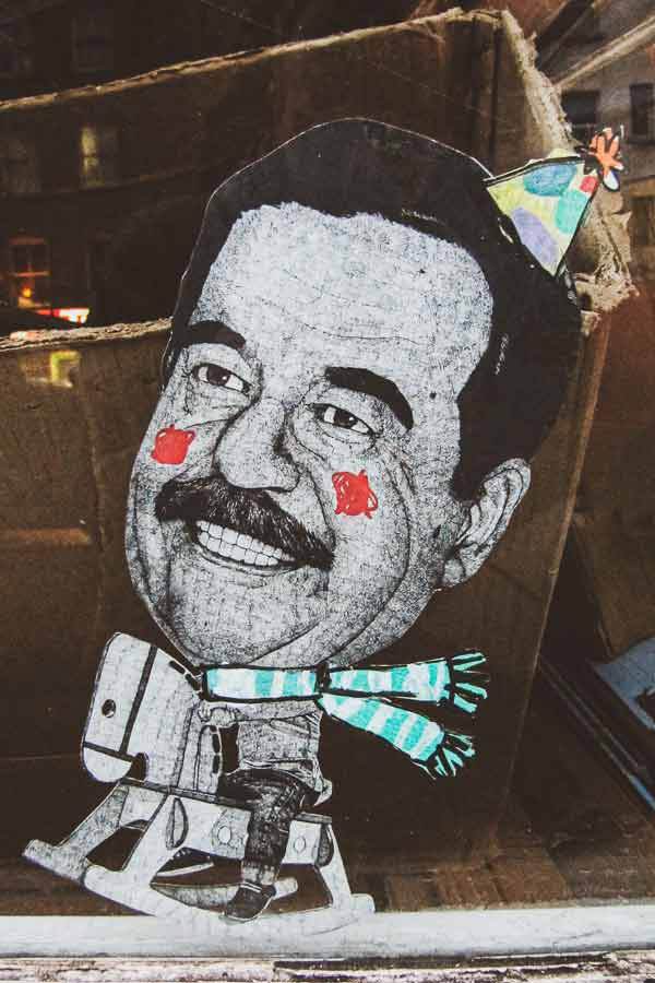 Shoreditch paste-up by HIN of a ridiculous Sadam Hussein as a kid on a toy horse