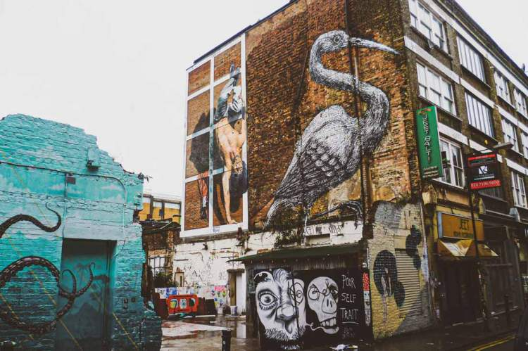 iconic mural by ROA on Hanbury Street of a giant crane (bird sacred to local Bengali) with next to it the mural by Martin Ron of a Tower of London Beefeater