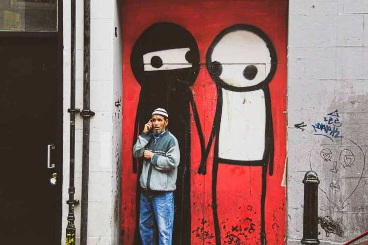 mural by Stik in Shoreditch featuring two figures holding hands, one representing white people, the other one represents the local Muslim community