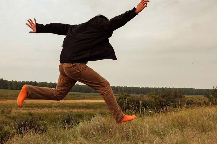 man running in a field wearing orange socks illustrating the funny Dutch saying: hero on socks