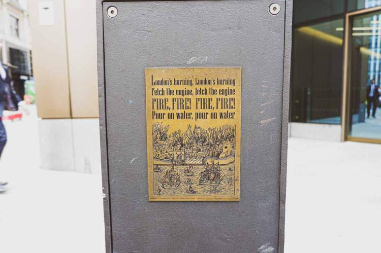 Plaque next to Monument saying: London's burning, London's burning, fetch the engine, fetch the engine, Fire, fire! Fire, fire! Pour on water, pour on water