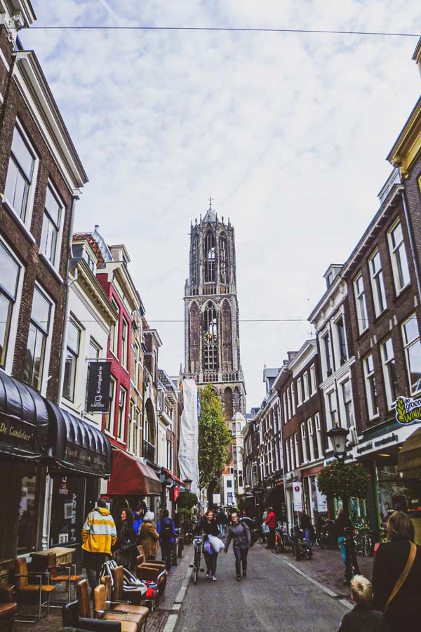 street view of a narrow street in Utrecht with the church tower the Dom in the background