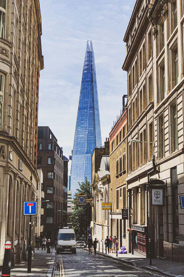 narrow historical street in London with The Shard peeking through at the end