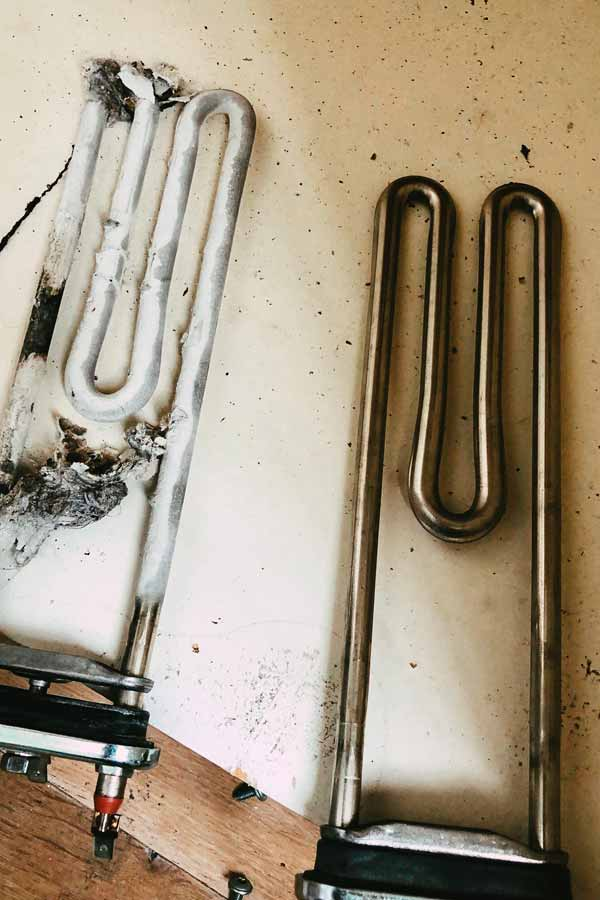 Washing machine heating elements one new and one covered in limescale