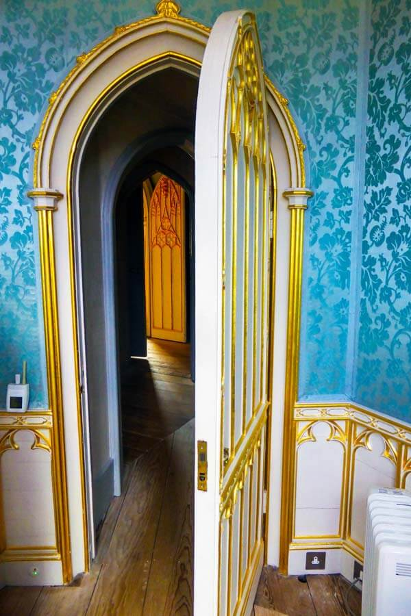room with blue wallpaper and gold-painted arches on wood panelling and the door