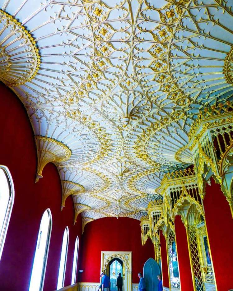 the Gallery Room in Strawberry Hill House is a long corridor with red wallpaper and a white ceiling heavily decorated with golden arches