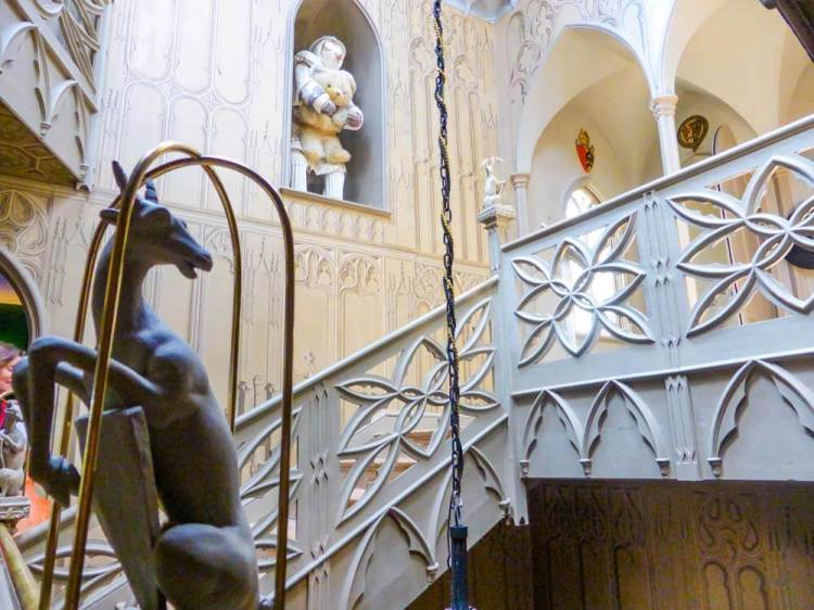white wooden decorated staircase at Strawberry Hill House with close-up of antelope decoration