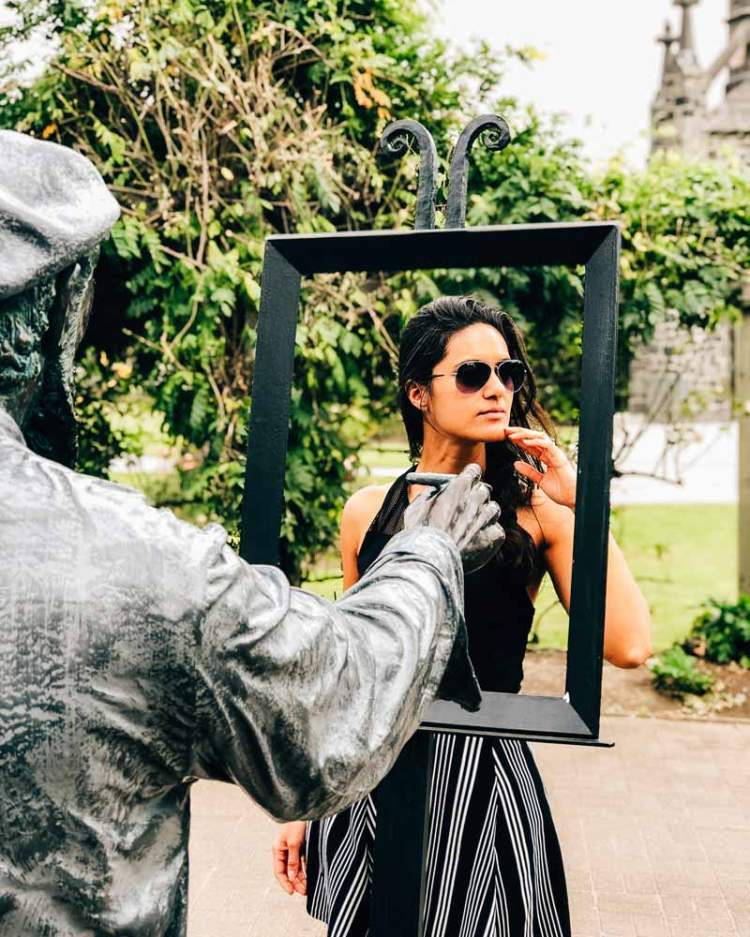 Zarina posing by an artwork in Akaroa, New Zealand