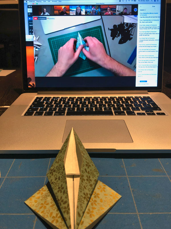 Learning how to fold a paper crane during the origami workshop with Paperboyo