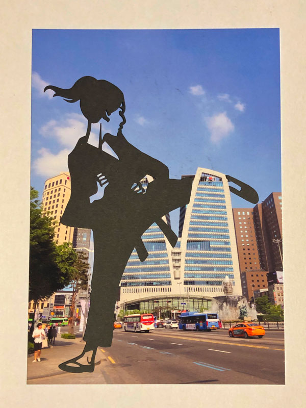 Photo of a Korean landmark with a papercut figure by Paperboyo of a taekwondoin placed in such a way it looks like the figure kicked the building in half