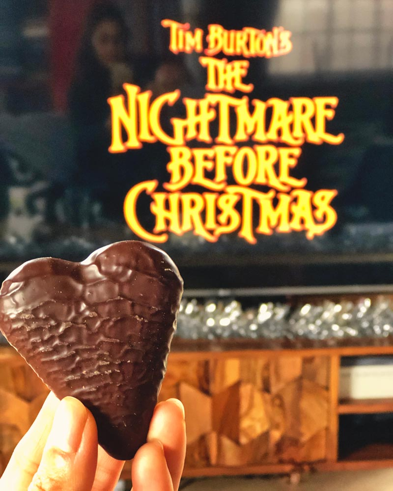 Zarina holding a chocolate heart-shaped biscuit with the TV in the background showing the credits for Tim Burton's The Nightmare Before Christmas