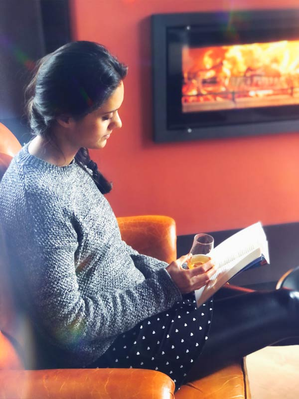 Zarina reading by the fireplace with a glass of whisky
